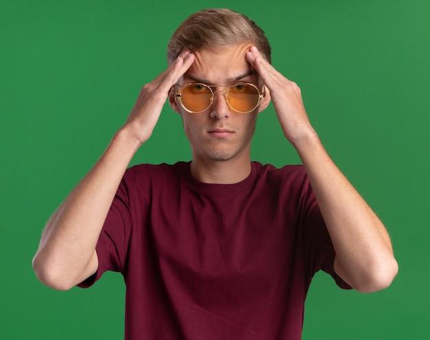 Zelfverzekerde jonge knappe kerel die rode overhemd en glazen draagt ?? die handen op voorhoofd zetten dat op groene muur wordt geïsoleerd