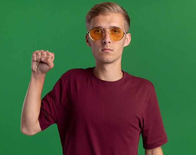 Zelfverzekerde jonge knappe kerel die rood overhemd en glazen draagt ?? die vuist houdt die op groene muur wordt geïsoleerd