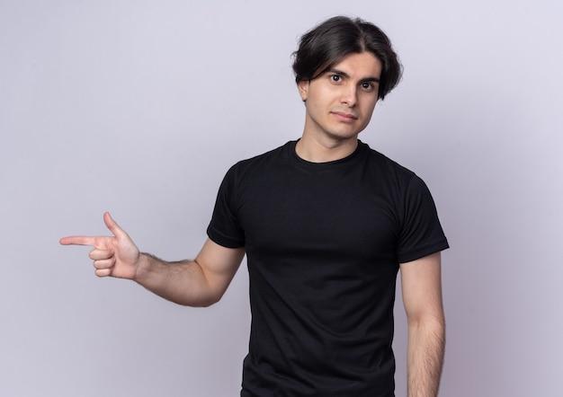 Zelfverzekerde jonge knappe kerel met zwarte t-shirtpunten aan de zijkant geïsoleerd op een witte muur met kopieerruimte