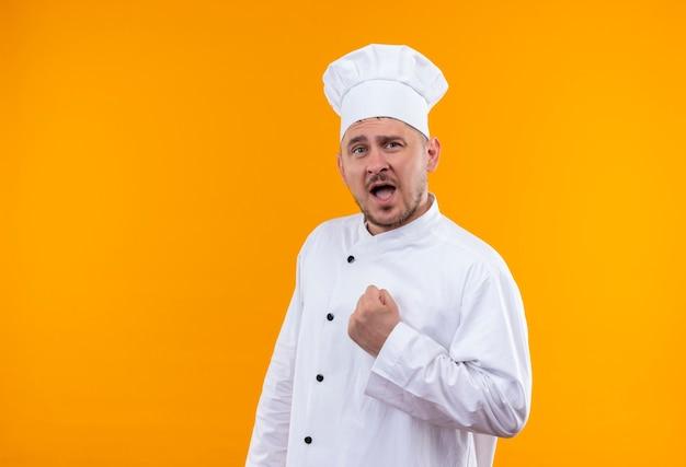 Zelfverzekerde jonge knappe kok in chef-kok uniform met gebalde vuist geïsoleerd op oranje muur orange