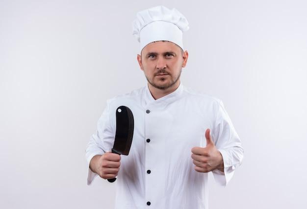 Zelfverzekerde jonge knappe kok in chef-kok uniform met hakmes en duim opdagen op geïsoleerde witte muur white
