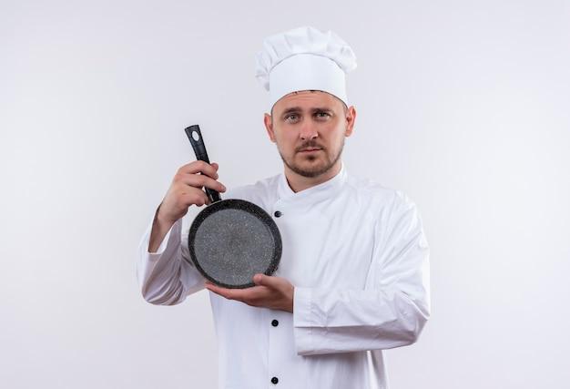 Zelfverzekerde jonge knappe kok in chef-kok uniform met koekenpan op geïsoleerde witte muur white