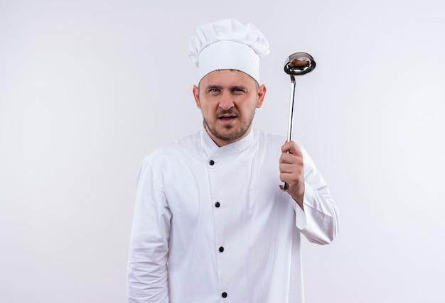 Zelfverzekerde jonge knappe kok in chef-kok uniform met pollepel op geïsoleerde witte muur white