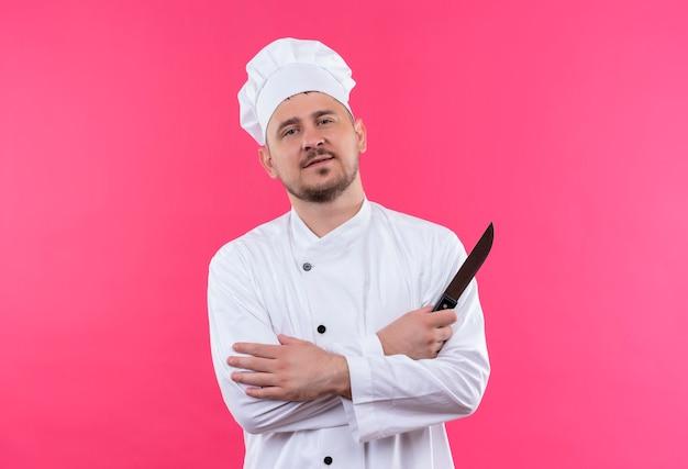 Zelfverzekerde jonge knappe kok in chef-kok uniform staande met gesloten houding en met mes geïsoleerd op roze muur
