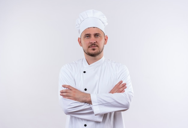 Zelfverzekerde jonge knappe kok in chef-kok uniform staande met gesloten houding geïsoleerd op een witte muur white