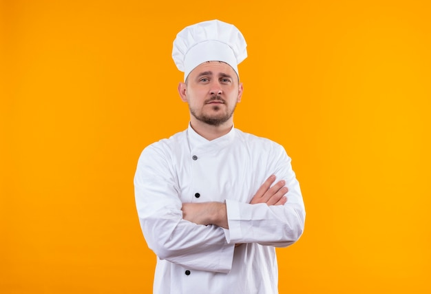 Zelfverzekerde jonge knappe kok in chef-kok uniform staande met gesloten houding geïsoleerd op oranje muur orange