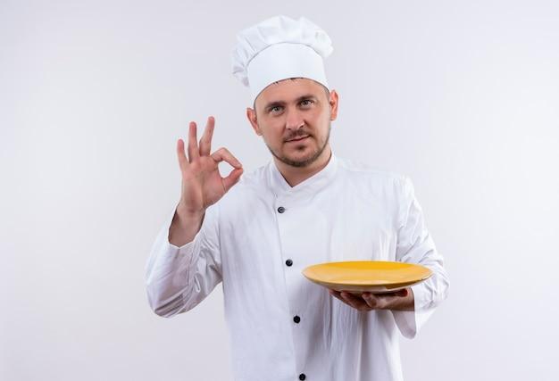 Zelfverzekerde jonge knappe kok in een uniforme chef-kok die een bord vasthoudt en een goed teken doet op een geïsoleerde witte muur