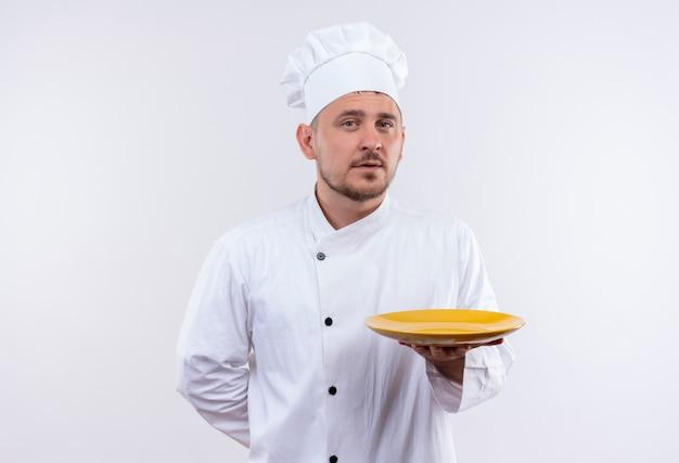 Zelfverzekerde jonge knappe kok in uniform met chef-kok bord op geïsoleerde witte muur