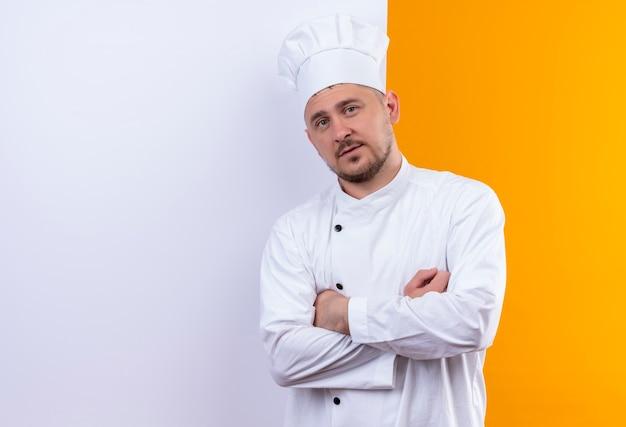 Zelfverzekerde jonge knappe kok in uniform van de chef-kok die achter een witte muur staat geïsoleerd op een oranje muur met kopieerruimte