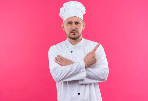 Zelfverzekerde jonge knappe kok in uniform van de chef-kok die de hand op de arm legt en naar de zijkant wijst, geïsoleerd op een roze muur
