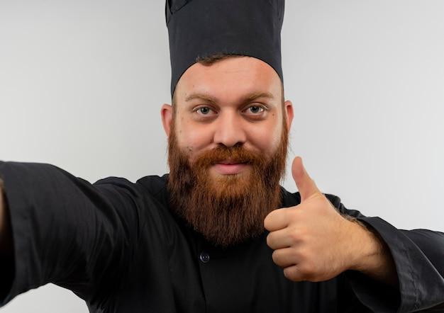 Zelfverzekerde jonge knappe kok in uniform van de chef-kok die de hand uitstrekt en duim toont die op een witte muur is geïsoleerd