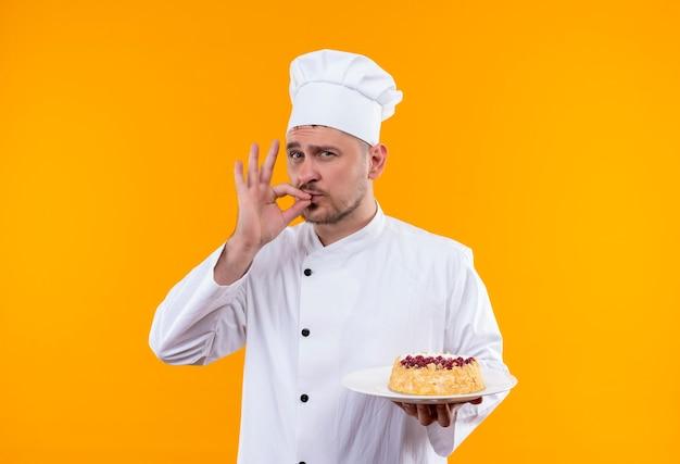Zelfverzekerde jonge knappe kok in uniform van de chef-kok die een bord cake vasthoudt en een smakelijk gebaar doet geïsoleerd op een oranje muur