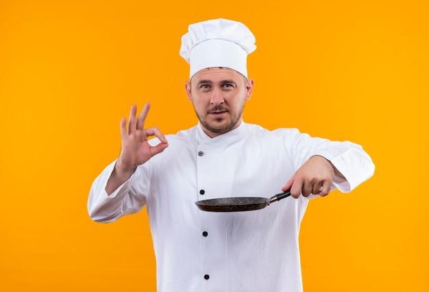 Zelfverzekerde jonge knappe kok in uniform van de chef-kok die een koekenpan vasthoudt en een goed teken doet dat op een oranje muur is geïsoleerd