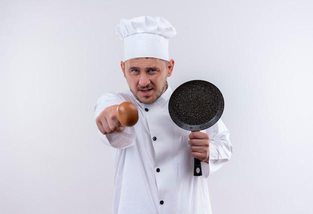 Zelfverzekerde jonge knappe kok in uniform van de chef-kok die een koekenpan vasthoudt en met een lepel op een geïsoleerde witte muur wijst