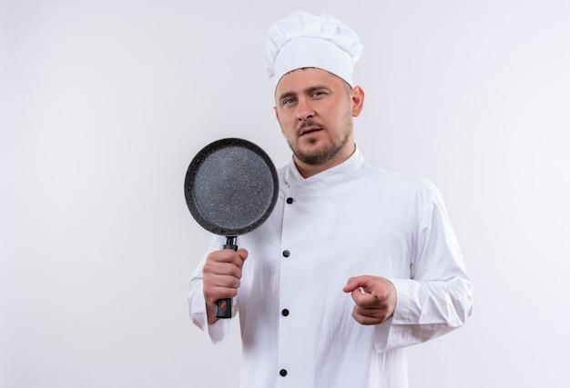 Zelfverzekerde jonge knappe kok in uniform van de chef-kok die een koekenpan vasthoudt en op een geïsoleerde witte muur wijst met kopieerruimte