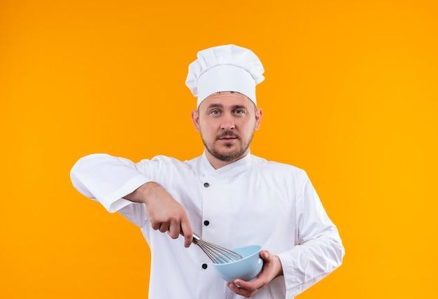 Zelfverzekerde jonge knappe kok in uniform van de chef-kok die kom vasthoudt en zwaait geïsoleerd op oranje muur