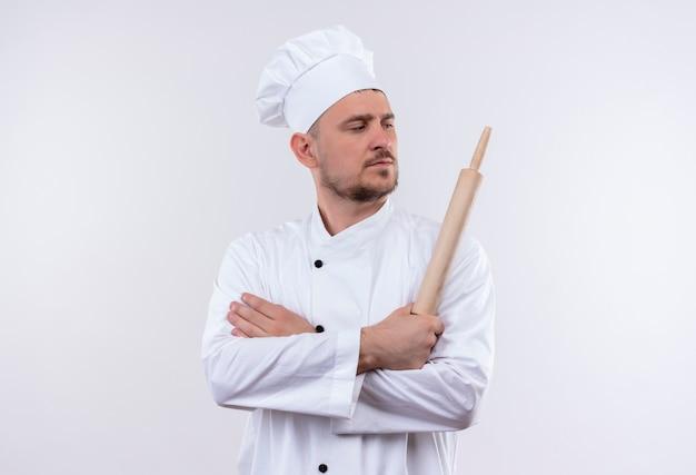 Zelfverzekerde jonge knappe kok in uniform van de chef-kok die met gesloten houding staat en deegroller vasthoudt en naar de zijkant kijkt die op een witte muur is geïsoleerd