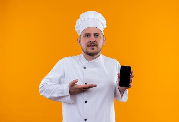 Zelfverzekerde jonge knappe kok in uniform van de chef-kok die mobiele telefoon vasthoudt en ernaar wijst, geïsoleerd op een oranje muur