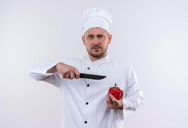 Zelfverzekerde jonge knappe kok in uniform van de chef-kok die peper vasthoudt en met een mes naar hem wijst, geïsoleerd op een witte muur