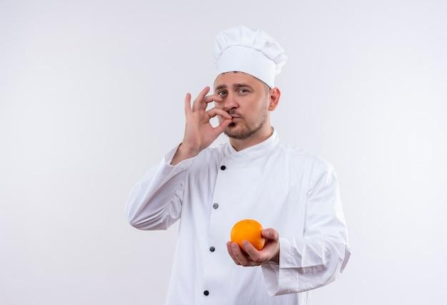 Zelfverzekerde jonge knappe kok in uniform van de chef-kok die sinaasappel vasthoudt en een smakelijk gebaar doet dat op een witte muur wordt geïsoleerd