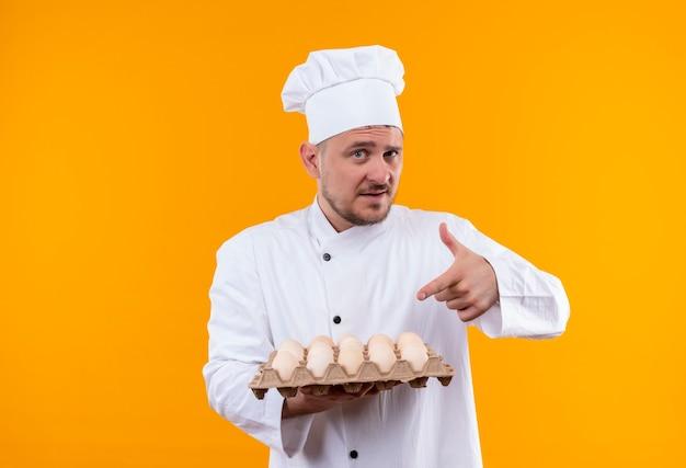 Zelfverzekerde jonge knappe kok in uniform van de chef-kok die vasthoudt en wijst naar een doos eieren geïsoleerd op een oranje muur