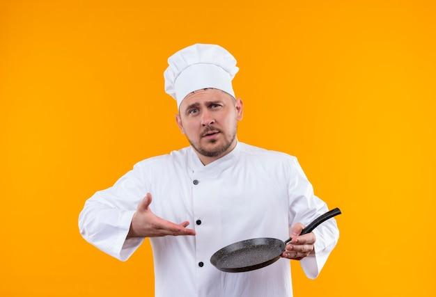 Zelfverzekerde jonge knappe kok in uniform van de chef-kok die vasthoudt en wijst naar een koekenpan geïsoleerd op een oranje muur