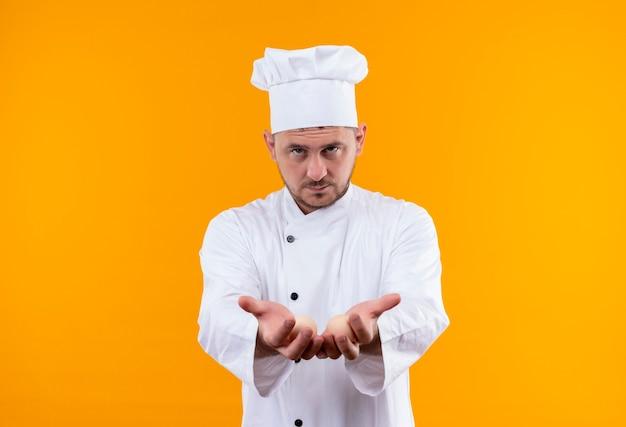 Zelfverzekerde jonge knappe kok in uniform van de chef-kok die zich uitstrekt en lege handen toont die op een oranje muur zijn geïsoleerd