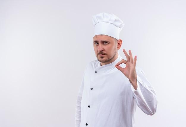 Zelfverzekerde jonge knappe kok in uniform van de chef-kok doet ok teken geïsoleerd op een witte muur met kopieerruimte