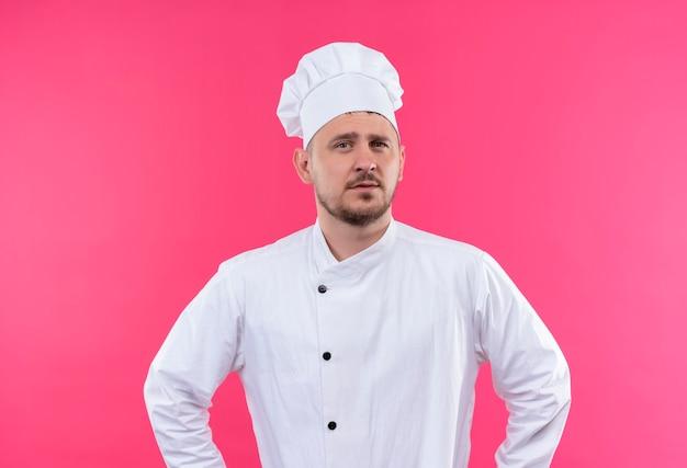 Zelfverzekerde jonge knappe kok in uniform van de chef-kok geïsoleerd op roze muur