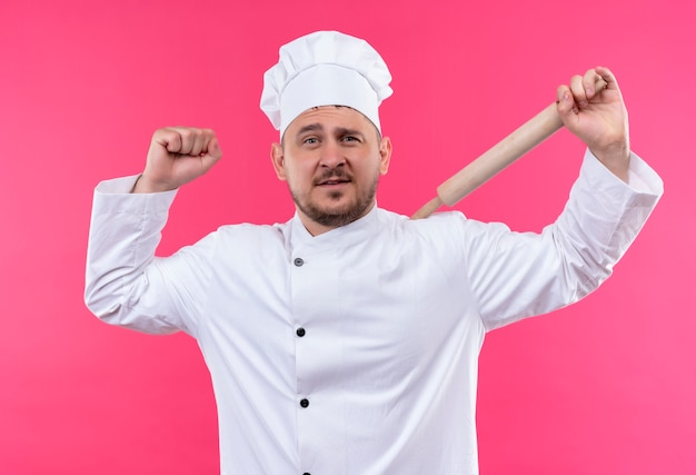 Zelfverzekerde jonge knappe kok in uniform van de chef-kok met deegroller gebaren sterk geïsoleerd op roze muur