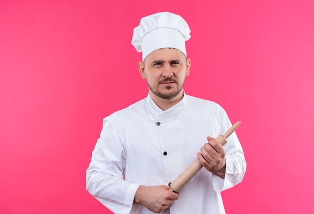 Zelfverzekerde jonge knappe kok in uniform van de chef-kok met deegroller geïsoleerd op roze muur