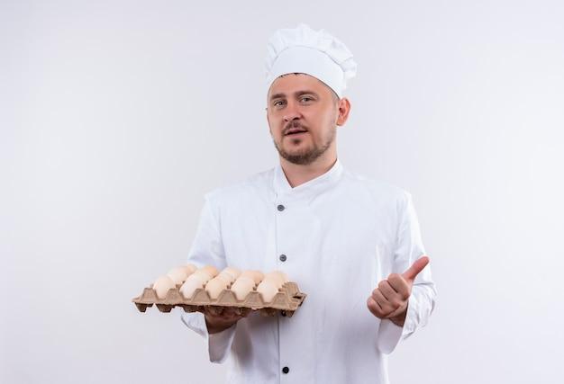 Zelfverzekerde jonge knappe kok in uniform van de chef-kok met doos eieren en duim opdagen geïsoleerd op een witte muur