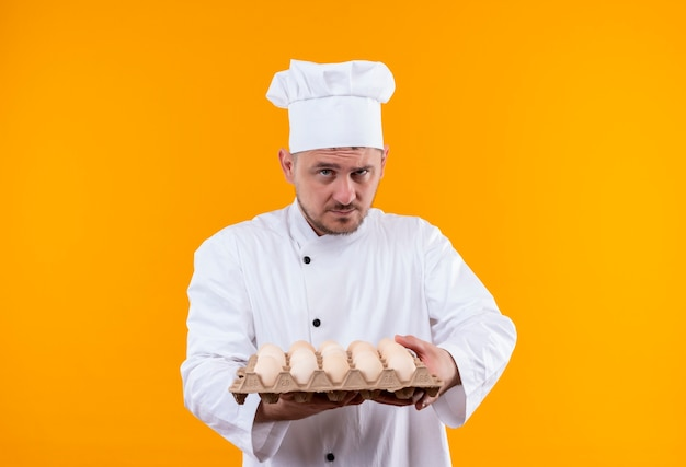 Zelfverzekerde jonge knappe kok in uniform van de chef-kok met doos eieren geïsoleerd op oranje muur
