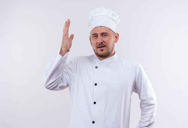 Zelfverzekerde jonge knappe kok in uniform van de chef-kok met opgeheven hand geïsoleerd op een witte muur