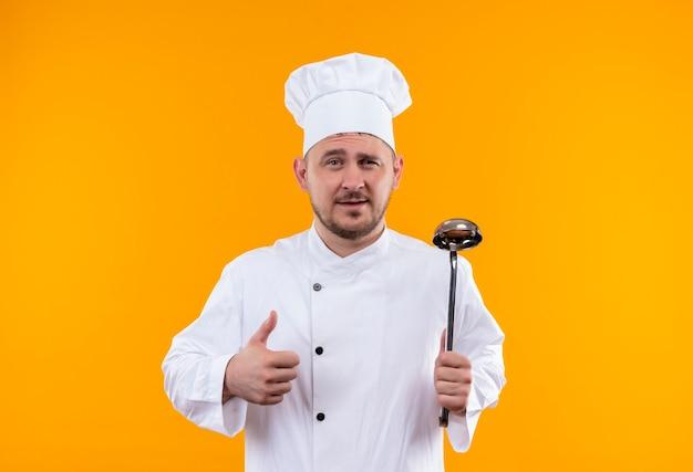 Zelfverzekerde jonge knappe kok in uniform van de chef-kok met pollepel en duim opdagen op geïsoleerde oranje muur met kopieerruimte