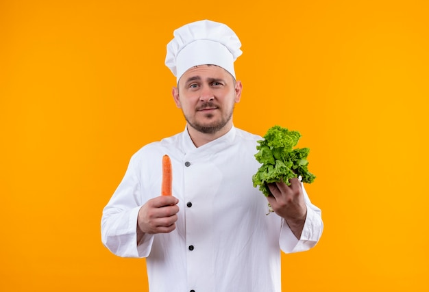 Zelfverzekerde jonge knappe kok in uniform van de chef-kok met sla en wortel geïsoleerd op een oranje muur