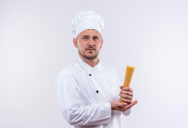 Zelfverzekerde jonge knappe kok in uniform van de chef-kok met spaghetti geïsoleerd op een witte muur