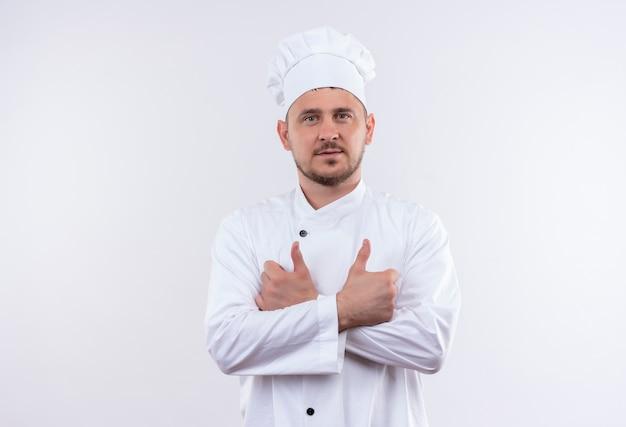 Zelfverzekerde jonge knappe kok in uniform van de chef-kok staande met gesloten houding duimen opdagen geïsoleerd op een witte muur