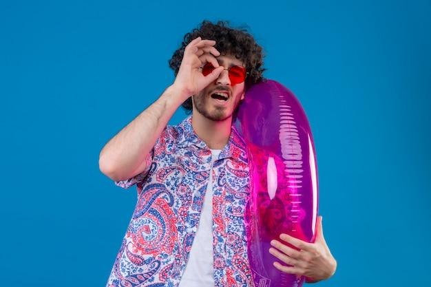 Zelfverzekerde jonge knappe krullende man die zonnebril draagt die zwemring houdt die blikgebaar op geïsoleerde blauwe ruimte met exemplaarruimte doet