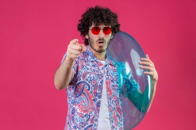 Zelfverzekerde jonge knappe krullende man die zonnebril draagt die zwemring houdt die op geïsoleerde roze ruimte met exemplaarruimte richt