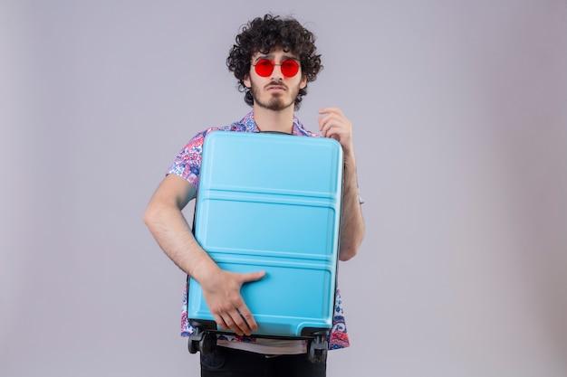 Zelfverzekerde jonge knappe krullende reizigersmens die zonnebril draagt die koffer houdt die op geïsoleerde witte ruimte met exemplaarruimte kijkt