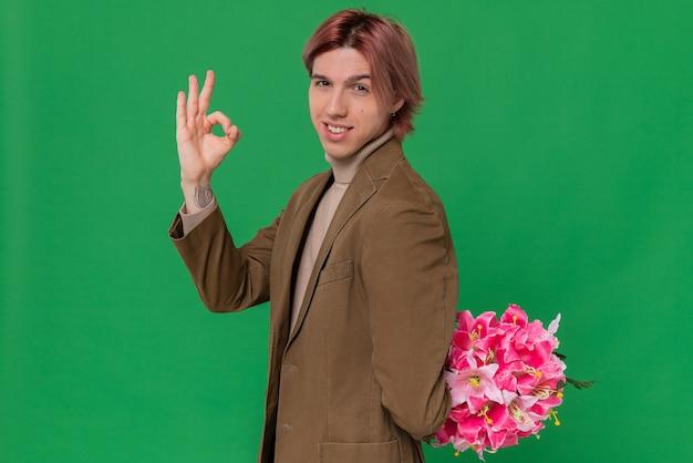 Zelfverzekerde jonge knappe man die een boeket bloemen achter zijn rug houdt en een goed teken gebaart