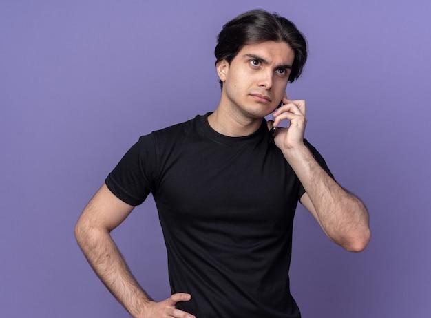 Zelfverzekerde jonge knappe man met zwart t-shirt spreekt op telefoon geïsoleerd op paarse muur
