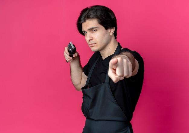 Zelfverzekerde jonge knappe mannelijke kapper in uniform met tondeuses en punten geïsoleerd op roze muur met kopie ruimte