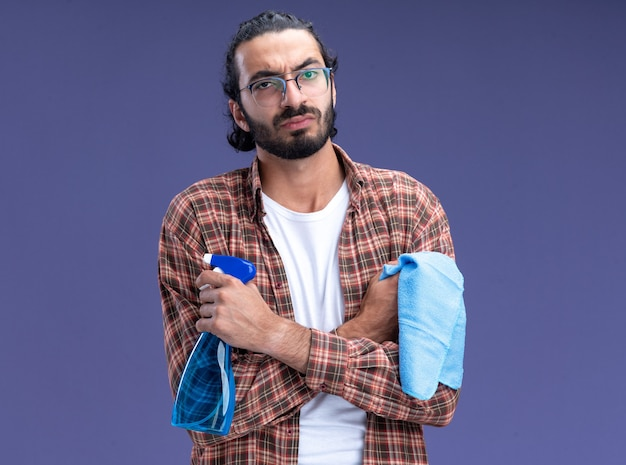 Zelfverzekerde jonge knappe schoonmaakster die de spuitfles van de t-shirtholding met lap kruist die handen op blauwe muur wordt geïsoleerd