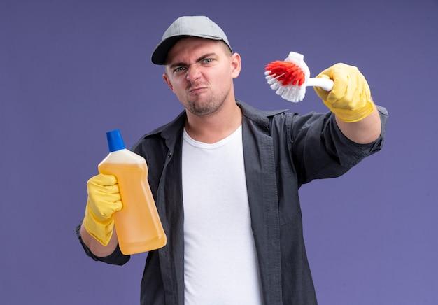 Zelfverzekerde jonge knappe schoonmaakster die t-shirt met pet en handschoenen draagt ?? die reinigingsmiddel houdt en borstel standhoudt die op paarse muur wordt geïsoleerd