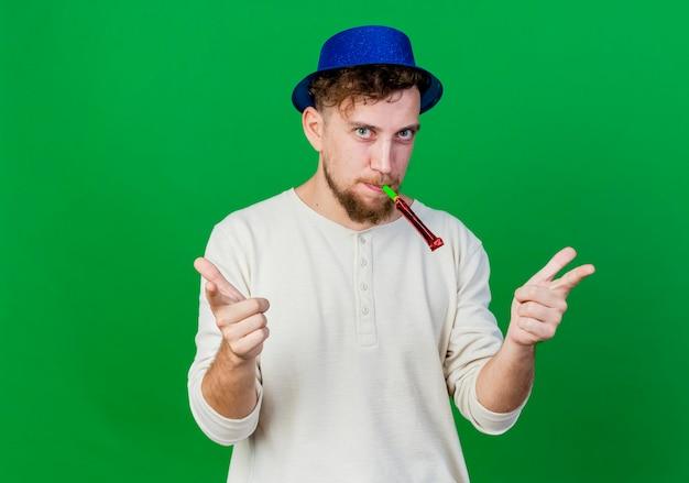 Zelfverzekerde jonge knappe slavische feestjongen die feestmuts draagt die partijblazer in mond houdt die aan voorzijde kijkt die je gebaar doet geïsoleerd op groene muur met exemplaarruimte