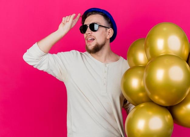 Zelfverzekerde jonge knappe slavische feestmens die feestmuts en zonnebril draagt ?? die ballonnen vasthoudt die naar de zijkant kijkt en verliezergebaar doet die tong toont die op roze muur wordt geïsoleerd