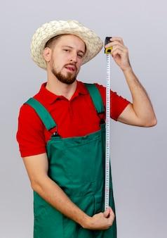 Zelfverzekerde jonge knappe slavische tuinman in uniform en hoed met tape meter op zoek