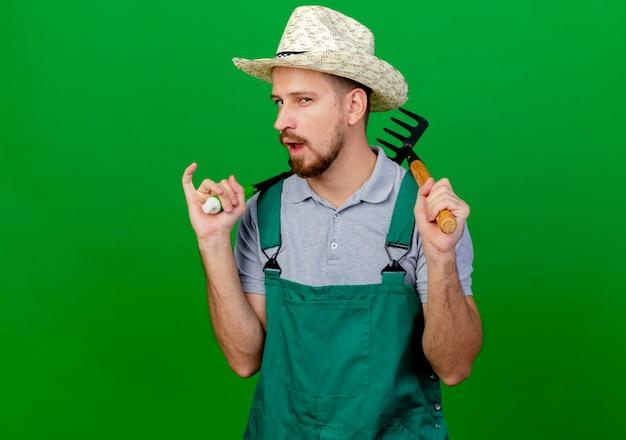 Zelfverzekerde jonge knappe slavische tuinman in uniform en hoed op zoek met snoeischaren en hark op schouders